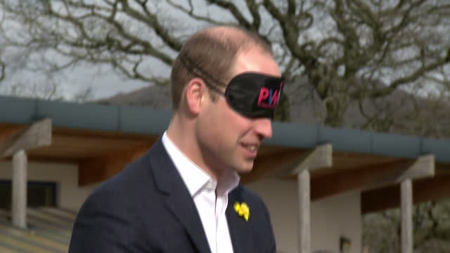 Exterior shots of Prince William taking part in a teamwork exercise putting on a blindfold as a group of children try to construct a tent following...