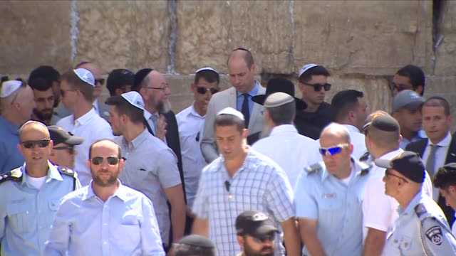 exterior shots of prince william walking away from the western wall and signing the guest book, surrounded by officials and chief rabbi and press,... - signierstunde stock-videos und b-roll-filmmaterial
