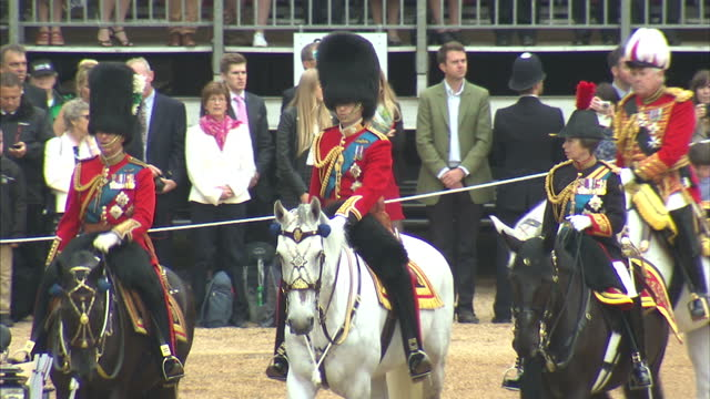exterior shots of princess anne, prince william and prince charles riding in ceremonial uniforms behind the queen's carriage during the inspection of... - 軍旗分列行進式点の映像素材/bロール