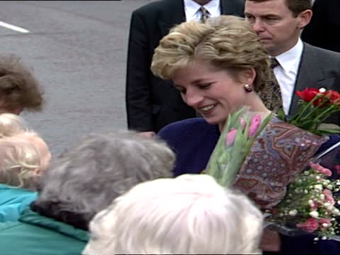 Exterior shots of Princess Diana meeting members of the public in Newcastle and being given flowers by women in road as Diana speaks to them and...