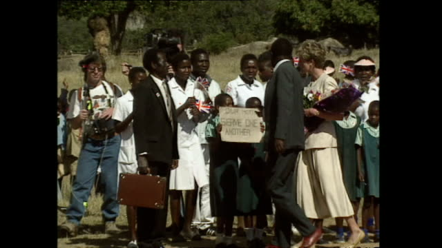 exterior shots of princess diana, princess of wales visiting red cross feeding station, holding flowers and meeting locals who are dancing during,... - conceptual symbol stock videos & royalty-free footage