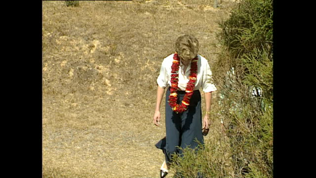 exterior shots of princess diana, princess of wales walking up hill to see view and taking in the landscape with officials wearing a flower garland... - フラワーアレンジメント点の映像素材/bロール