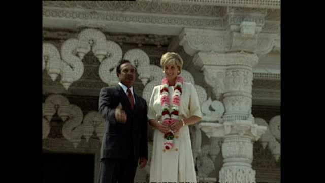 stockvideo's en b-roll-footage met exterior shots of princess diana receiving a bindi on her forehead and a garland of flowers on her visit to shri swaminarayan mandir hindu temple on... - guirlande