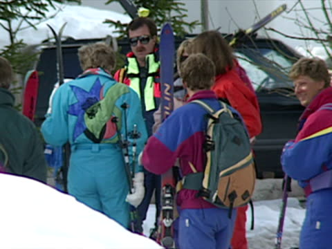 Exterior shots of Princess Diana wearing turquoise blue ski outfit and walk with Prince Harry and Prince William along with entourage all carrying...