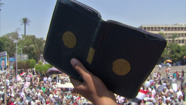 Exterior shots of Pro Mohamed Morsi crowds chanting along with man at front on stage with people holding Quran up and others waving Egyptian flag...