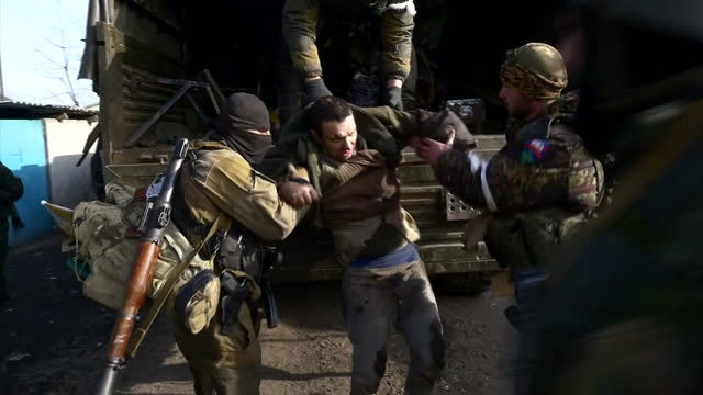 Exterior shots of pro Russian rebel soldiers dragging a captured Ukrainian soldier wounded from the back of an army lorry on February 19 2015 in...