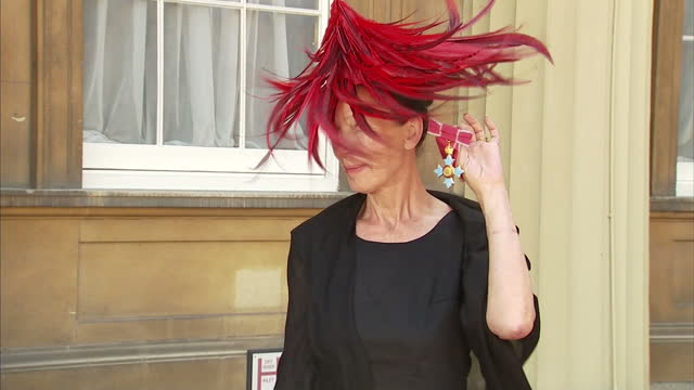 exterior shots of professor katharine hamnett fashion designer in court yard of buckingham palace wearing striking red feather hat posing with obe... - katharine hamnett stock videos & royalty-free footage