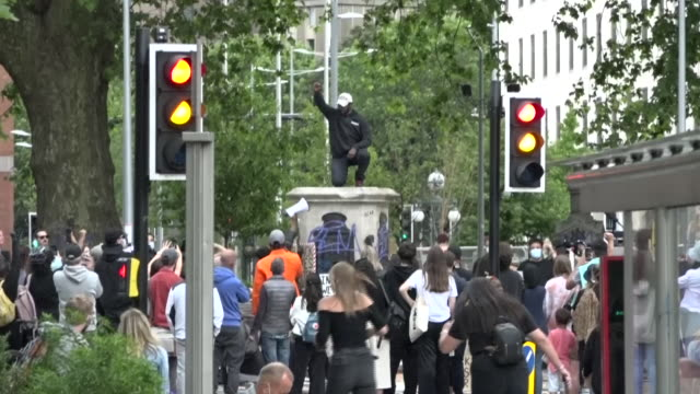 vidéos et rushes de exterior shots of protester climbing on top of taking a knee on the plinth where a statue of slave trader, edward coltson, stood earlier that day... - statue
