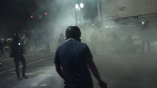 exterior shots of protesters chanting and facing off with federal agents as tear gas smoke fills the air on 25 july 2020 in portland, oregon, usa - portland oregon stock videos & royalty-free footage