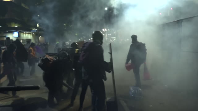 exterior shots of protesters facing off against fedreal agents as both groups use leaf blowers to disperse tear gas smoke on 25th july 2020 in... - portland oregon stock videos & royalty-free footage