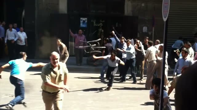 vídeos de stock, filmes e b-roll de exterior shots of protesters fighting on the streets of aleppo hitting each other with sticks exterior shots of violent protests and clashes sky news... - arab spring