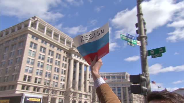 Exterior shots of protesters gathered outside the Department of Justice holding placards and signs calling for Attorney General John Sessions to...