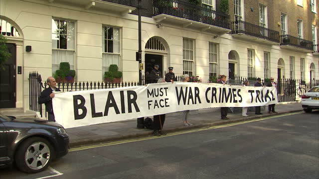 exterior shots of protesters holding a banner reading blair must face war crimes trial on july 6 2016 in london england - war crimes trial stock videos and b-roll footage