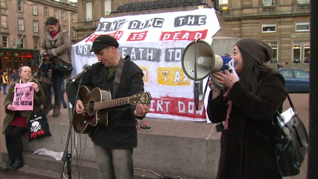 exterior shots of protesters in centre of glasgow cheering and chanting after death of baroness thatcher demonstrators celebrate death of thatcher on... - ボブ・マーリー点の映像素材/bロール