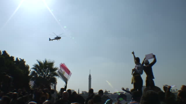 exterior shots of protesters in tahrir square, cairo, calling for the overthrow of hosni mubarek, as an egyptian army helicopter circles overhead... - egypt stock videos & royalty-free footage