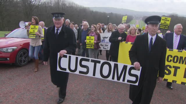 exterior shots of protesters marching along road to stormont carrying placards banners including sinn fein leader michelle o'neill demonstrating... - sinn fein stock videos & royalty-free footage