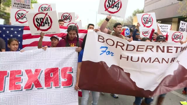 Exterior shots of protesters marching through Austin during a day of action for immigrants and refugee rights on February 28 2017 in Austin Texas