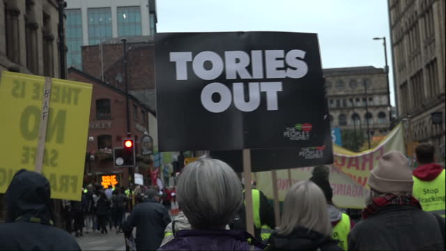 Exterior shots of protesters marching through central Manchester many holding placards woth antiConservative slogans during an antiausterity...