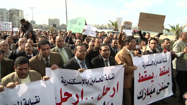 exterior shots of protesters marching with banners posters calling for president hosni mubarak to step down on january 31 2011 in alexandria egypt - revolution stock videos & royalty-free footage