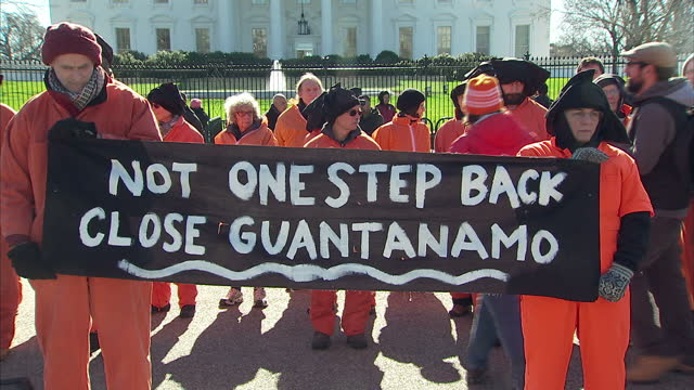 exterior shots of protesters outside the white house many clad in orange jump suits and hoods holding protest banners calling for the closure of the... - camp x ray stock videos & royalty-free footage