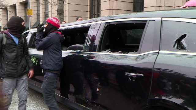 Exterior shots of protesters stood around and on top of a limousine which has been extensively damaged including having had most of its windows...