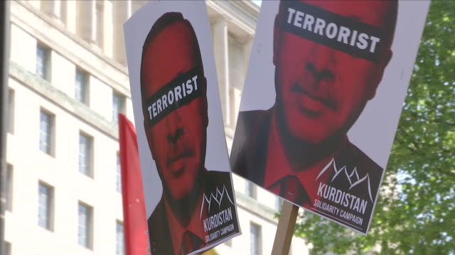 vídeos de stock, filmes e b-roll de exterior shots of protesters stood during an antierdogan demonstraion outside downing street holding various banners and placards 'dictator murderer... - stop placa em inglês