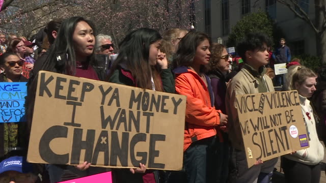 exterior shots of protesters stood holding banners and listening to a speech during a demonstration demanding the end to gun violence on 24th march... - march for our lives stock videos & royalty-free footage