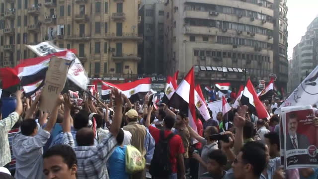 vídeos de stock, filmes e b-roll de exterior shots of protesters waving egyptian flags in protests calling for a new president and a fair election on june 18 2012 in cairo egypt - arab spring