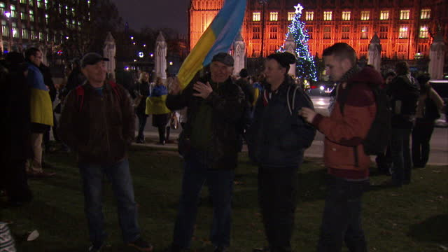 Exterior shots of protesters wearing Ukrainian flag holding up 'Vote Human Rights' posters protester waving Ukrainian flag in front of clock tower in...