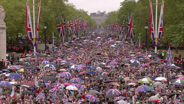 exterior shots of public gathered outside buckingham palace and at the mall some holding umbrellas which have great britain flag design and others... - diamond jubilee stock videos & royalty-free footage