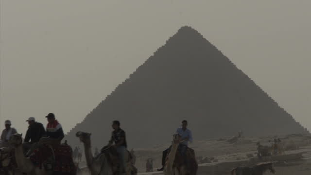 vídeos de stock e filmes b-roll de exterior shots of pyramid of khafre and subsidiary pyramids people riding camels on november 11 2014 in cairo egypt - pyramid