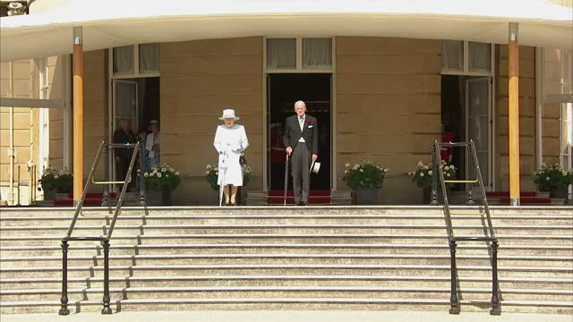 Exterior shots of Queen Elizabeth II and Prince Philip Duke of Edinburgh arriving at garden party in the grounds of Buckingham Palace and meeting...
