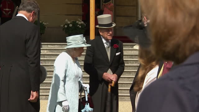 Exterior shots of Queen Elizabeth II and Prince Philip Duke of Edinburgh meeting guests at a garden party in the grounds of Buckingham Palace on 1st...
