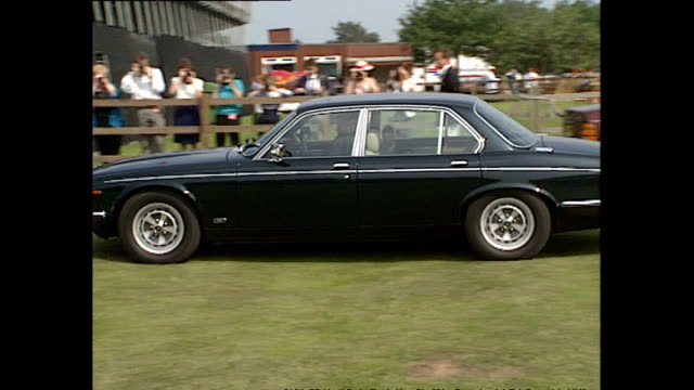 exterior shots of queen elizabeth ii arriving at royal berkshire polo club match driving a car shots of royal standard flag being raised on july 28... - elizabeth ii stock videos & royalty-free footage