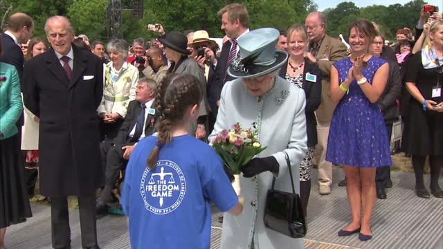 Exterior shots of Queen Elizabeth II departing Magna Carta 800th Anniversary event being given flowers by young girl and talking to other...