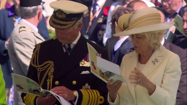 Exterior shots of Queen Elizabeth II Duke of Edinburgh Prince Philip Prince of Wales Prince Charles and the Duchess of Cornwall standing reading a...