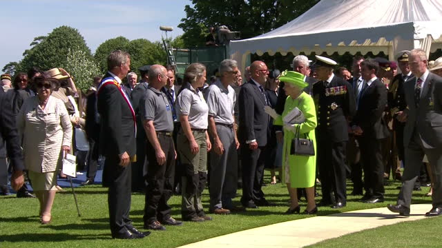 vídeos de stock e filmes b-roll de exterior shots of queen elizabeth ii greeting var people in a line at the d day remembrance ceremony in bayeux, with prince philip the duke of... - var