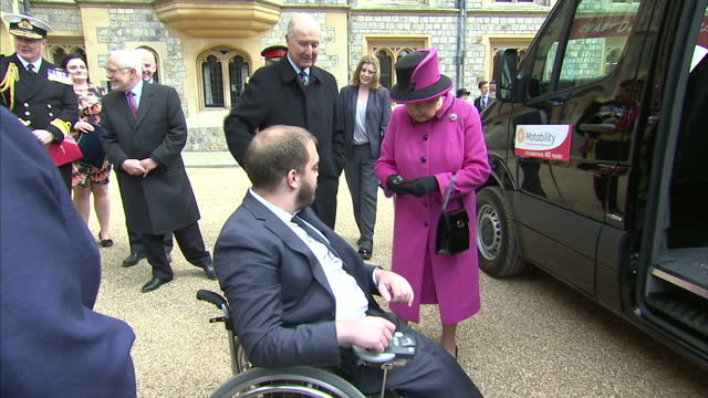 Exterior shots of Queen Elizabeth II meeting a family who lease a specially adapted vehicle through the Motability charity during a ceremony to mark...