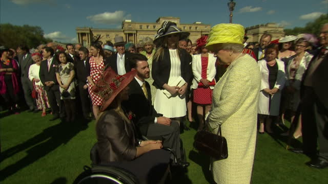 stockvideo's en b-roll-footage met exterior shots of queen elizabeth ii meeting anna turney and ben sneesby paralympian sit skiers and talking to them about their sport at buckingham... - yeomen warder