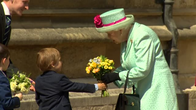 exterior shots of queen elizabeth ii receiving flowers from children for her 93rd birthday upon departure after an easter sunday service at st... - queen royal person stock videos & royalty-free footage