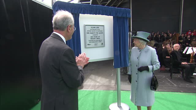 vídeos de stock e filmes b-roll de exterior shots of queen elizabeth ii unveiling plaque at magna carta anniversary event and meeting various officials at event shaking hands and... - magna carta documento histórico