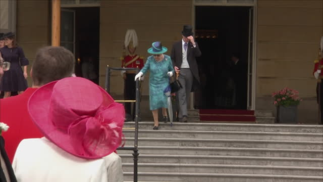 exterior shots of queen elizabeth ii walking down the palace steps wearing sunglasses and begins meeting her guests at the buckingham palace garden... - prinzessin stock-videos und b-roll-filmmaterial