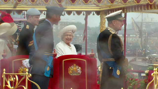 Exterior shots of Queen Elizabteh II Prince Philip Prince Charles Prince William and Prince Harry on Royal Barge Spirit of Chartwell waving at...