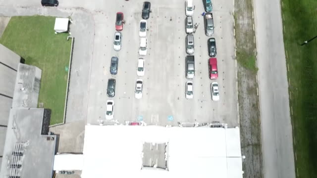 vídeos y material grabado en eventos de stock de exterior shots of queues of cars at a drive through covid-19 testing centre and soldiers assisting and taking information from the car passengers on... - material médico