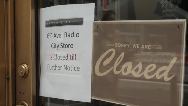 vídeos y material grabado en eventos de stock de exterior shots of quiet 6th avenue with a notice of closure in the door of the radio city music hall store due to the coronavirus pandemic on 20... - radio city music hall