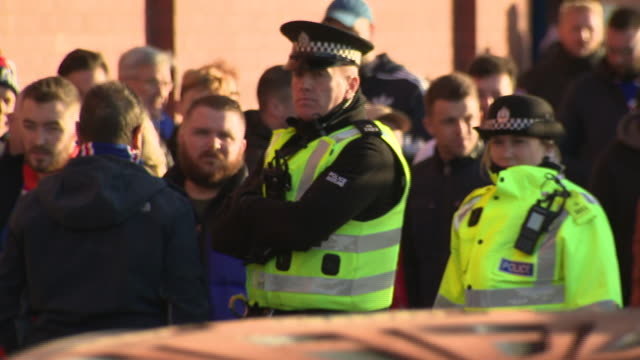 vídeos y material grabado en eventos de stock de exterior shots of rangers' ibrox stadium on an old firm matchday with programme sellers police and security outside as fans queue to enter turnstiles... - glasgow escocia