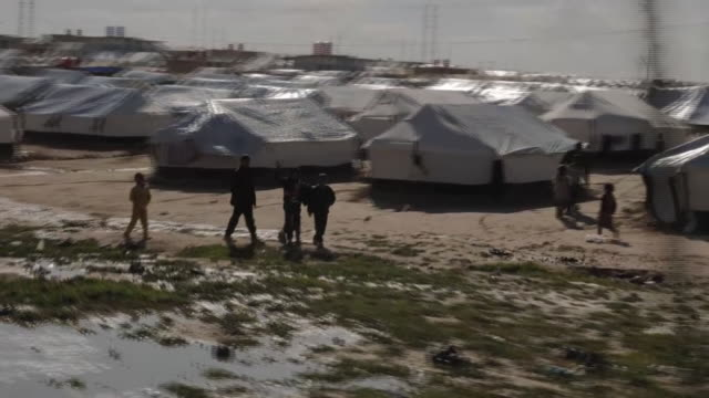 stockvideo's en b-roll-footage met exterior shots of refugee camp and some anon refugee children sitting by fence in al hawl on 2 march 2019 in northern syria, syria - isis