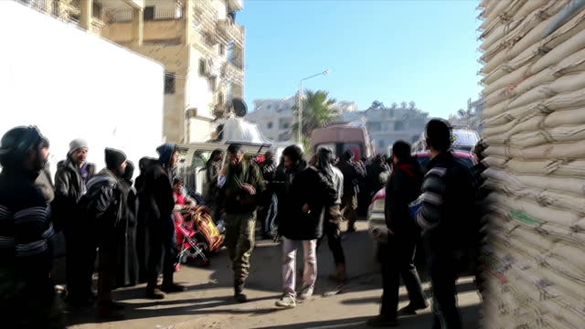 exterior shots of refugees from east aleppo in streets awaiting evacuation on december 16 2016 in aleppo syria - シリア難民問題点の映像素材/bロール