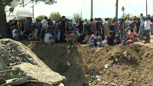 Exterior shots of refugees in a makeshift camp on the Greek side of the Greek Macedonian border as volunteer aid workers distribute supplies to them...