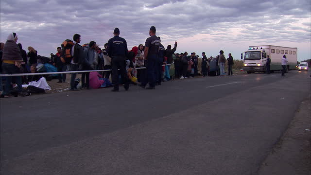 exterior shots of refugees waiting in a holding area to be taken onward into munich police patrol the area as a coach arrives to take refugees and a... - flüchtlingslager stock-videos und b-roll-filmmaterial